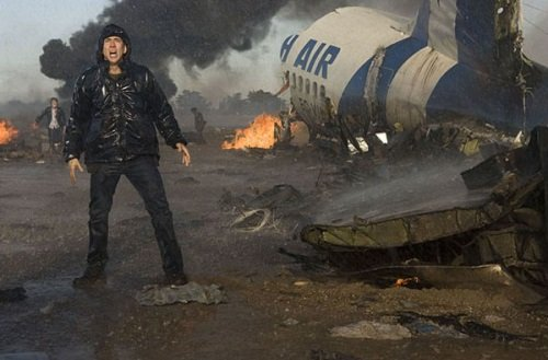 Nicolas Cage in front of a crashed plane